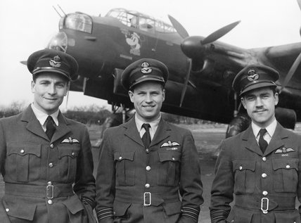 Wing Commander Guy Gibson (centre), CO of No. 106 Squadron RAF, with his two Flight Commanders, Squadron Leader J H Searby (left) and Squadron Leader P Ward-Hunt, at Syerston, on the completion of Gibson's tour of operations, March 1943.
