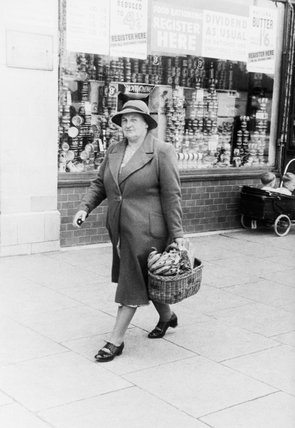 A housewife with a shopping basket full of bananas after a visit to the Co-Op store on Westhorne Avenue, Eltham in London, 1940.