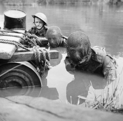 Members of the Doncaster Home Guard, two wearing camouflage net veils over their faces, swim across a river during an assault exercise, 20 July 1942.
