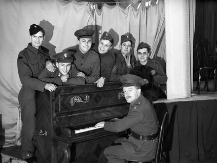 The concert party of 1st Battalion King's Shropshire Light infantry rehearsing at La Belle Porte near Mouchin in France, 28 December 1939.