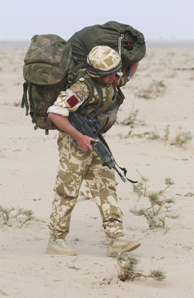 A paratrooper serving with 1st Battalion, The Parachute Regiment after a practice jump in Kuwait, during preparations for Operation 'TELIC', the invasion of Iraq, 16 March 2003.