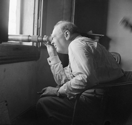 Winston Churchill uses a telescope to watch an assault against enemy positions north of Florence, from the observation post of a battery of the 66th (Lowland) Medium Regiment, Royal Artillery, 20 August 1944.