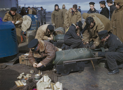 Fleet Air Arm personnel fusing bombs for Fairey Barracudas on the flight deck of HMS VICTORIOUS, before Operation 'Tungsten', the attack on the German battleship TIRPITZ in Alten Fjord, Norway, April 1944.