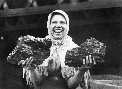 A female pit brow worker in Lancashire during 1918 holding two large chunks of coal.