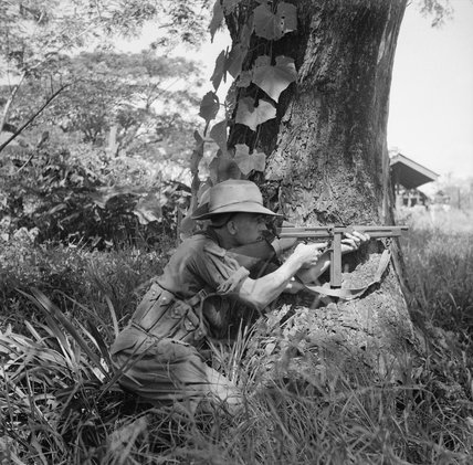 A fusilier of the Royal Scots provides covering fire with his Thompson sub-machine gun in the village of Namma in Burma, October 1944.