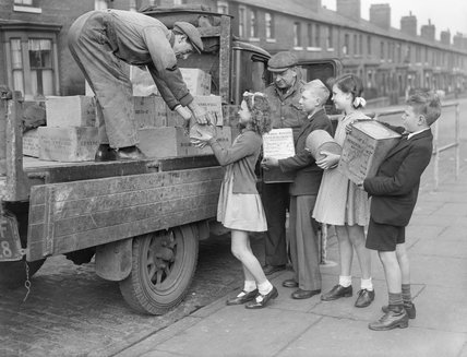 Four children help load tins of Meredith and Drew Ltd. 'Welfare Biscuits' onto a lorry for dispatch to civilians in liberated Europe, 1945.
