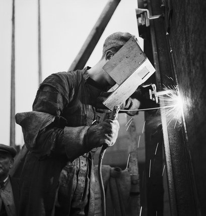 Shipbuilding: A welder, wearing a protective mask, at work in a British shipyard.