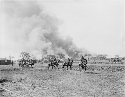 Gun teams moving forward to pull their guns out of position whilst huts and stores at Omiecourt are burnt to prevent them falling into the hands of the advancing Germans, 24 March 1918.
