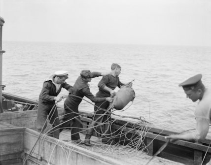 Throwing mines attached to nets overboard from a British Drifter.