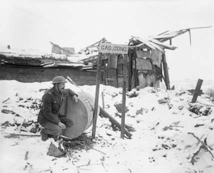 Gas sentry of the Royal Garrison Artillery on lookout duty with his gas gong. Combles, March 1917.