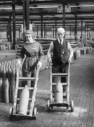 A young woman and an old man, both workers at Chilwell munitions factory, transport shells across the factory floor.