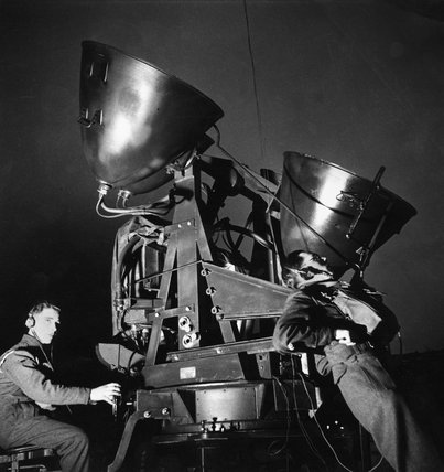 A Royal Artillery searchlight unit's sound locator monitors the night sky at the height of the Blitz, London, 1940
