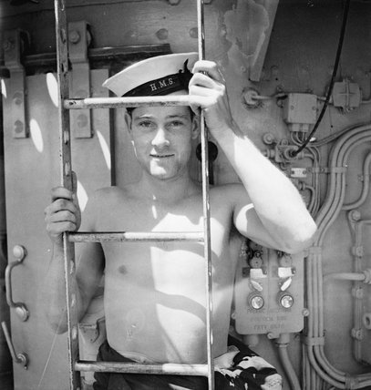 A sailor poses by a ladder in the sunlight on board the armed merchant cruiser HMS ALCANTARA en route to Sierra Leone, 1942