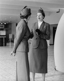 Two air stewardesses talking in the main hall of the Queen's Building at Heathrow Airport: 1953