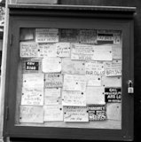 A collection of cards tacked to a board inside a locked frame advertising the services of female sex workers. c.1955