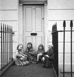 Four girls sitting outside a front door. c.1955