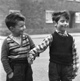 Two boys hold hands in street. c.1955