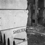 Crumbling wall painted with the word 'Shelters'. c.1955