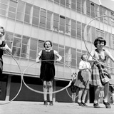 Children playing with hoops in school playground: 1959
