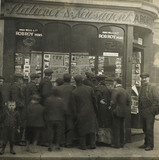 A crowd gathered around an East End newsagents window display: c.1900