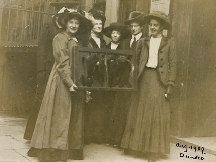 Five suffragettes holding a broken window pane: 1912