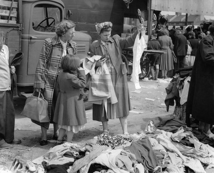 Women looking at clothes at a street market in Mile End: c. 1948