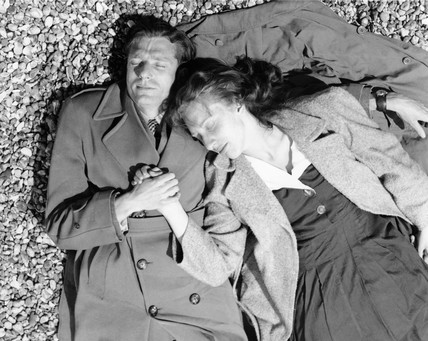 A couple lying together on Brighton Beach: c. 1955