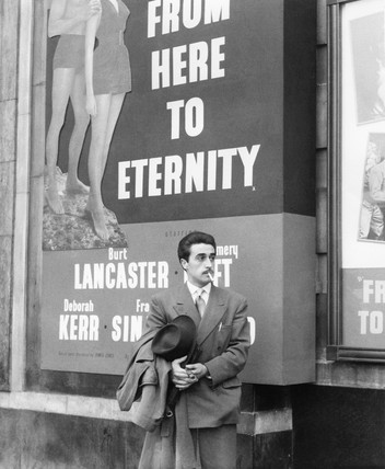 A man standing outside the Odeon cinema at Hyde Park Corner: c. 1953