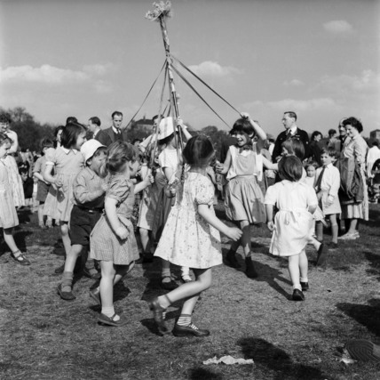 Children dance around a maypole on May Day; 1956