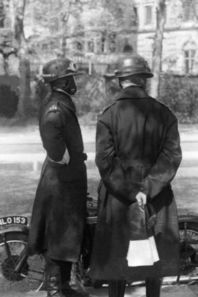 Police officers looking at a motorbike; 1940