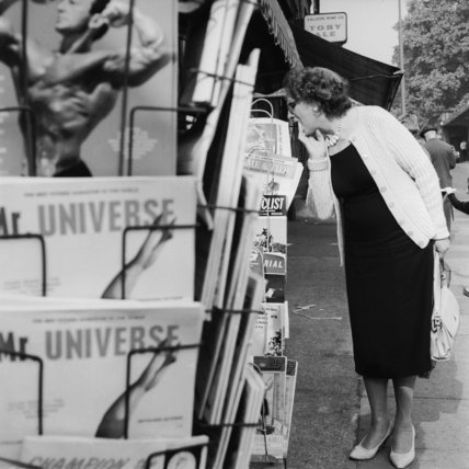 Woman browsing magazines at a newsagents; 1965