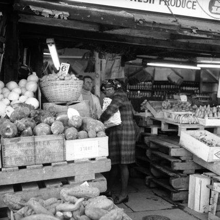 Woman buying  fruit and vegetables from a grocer;c.1960