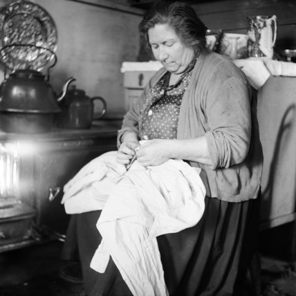 A gypsy woman sewing in her caravan
