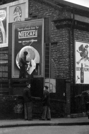 A billboard paster works to complete an advert in Chalk Farm Road, 1957