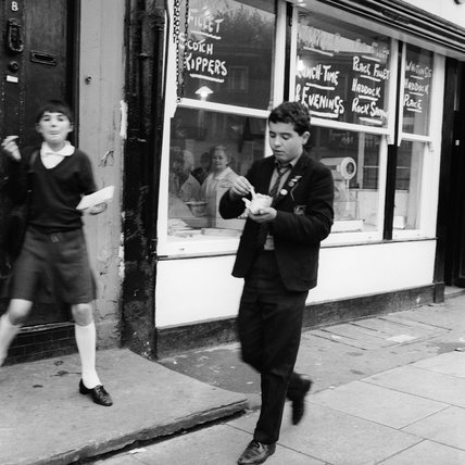 A boy eating take away chips in the street; 1965