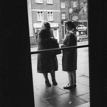 Two women standing talking on a street in Kentish Town