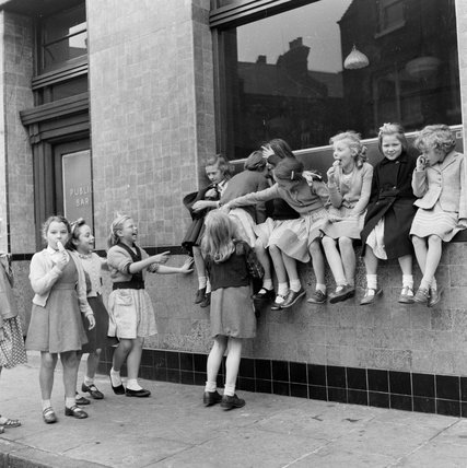 Children seated on the windowsill of a house; c. 1956