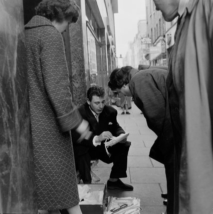 Street trader selling jewellery in Soho; c.1955