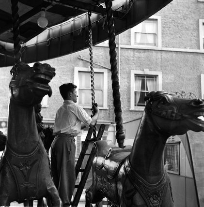 Fun fair worker cleaning the carousel; 1955
