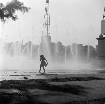 Little girl running through the water fountains in the Festival Gardens; 1955