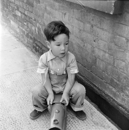 Boy playing with a toy train; c.1955