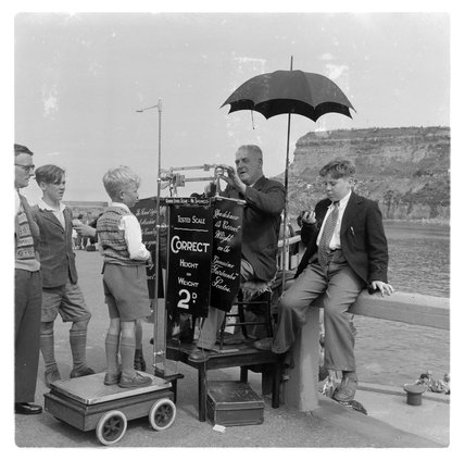 Young boy being measured by the seaside in Brighton; c 1955