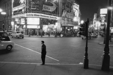 Lone man in Piccadilly at night; 1960