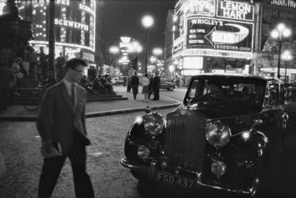 A man cuts across traffic at Piccadilly Circus; 1960