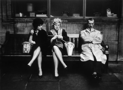 Two women and a man sit on a bench: 1961