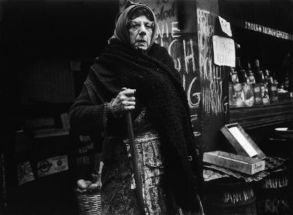 Woman outside a market stand: 1961