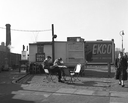 Two men sit at tables reading outside a roadside cafe. c.1955