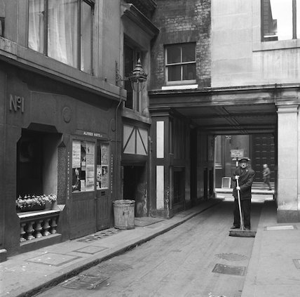 Street sweeper sweeping an alleyway. c.1955
