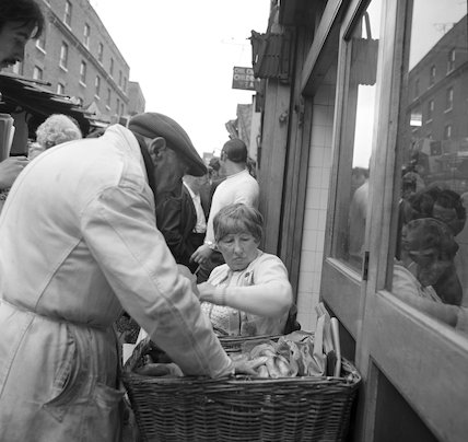 Man reaches into a basket full of bagels. c.1955