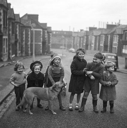 Children gathered in street with dog. c.1955